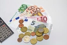 Verschiedene Euroscheine und Geldmünzen vor weißem Hintergrund